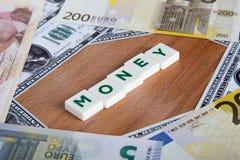 Palabra del dinero con las letras entre billetes de banco Fotos de archivo