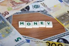 Palabra del dinero con las letras entre billetes de banco Foto de archivo libre de regalías