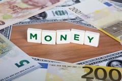Palabra del dinero con las letras entre billetes de banco Fotografía de archivo