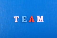 Palabra del EQUIPO en el fondo azul compuesto de letras de madera del ABC del bloque colorido del alfabeto, espacio de la copia p Fotografía de archivo
