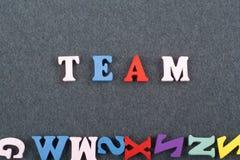 Palabra del EQUIPO en el fondo negro compuesto de letras de madera del ABC del bloque colorido del alfabeto, espacio del tablero  Imagen de archivo libre de regalías