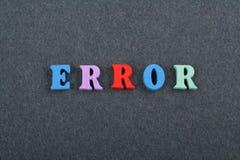 Palabra del ERROR en el fondo negro compuesto de letras de madera del ABC del bloque colorido del alfabeto, espacio del tablero d Imagen de archivo libre de regalías