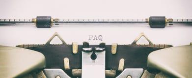 Palabra del FAQ con mayúsculas en una hoja de la máquina de escribir Foto de archivo libre de regalías