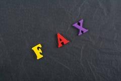 Palabra del FAX en el fondo negro compuesto de letras de madera del ABC del bloque colorido del alfabeto, espacio del tablero de  Imagenes de archivo