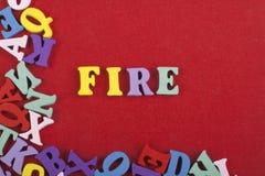 Palabra del FUEGO en el fondo rojo compuesto de letras de madera del ABC del bloque colorido del alfabeto, espacio de la copia pa Foto de archivo