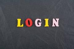 Palabra del INICIO DE SESIÓN en el fondo negro compuesto de letras de madera del ABC del bloque colorido del alfabeto, espacio de Fotos de archivo