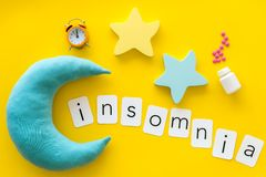 Palabra del insomnio, píldoras, luna, srars, alarma para la ayuda a bajar concepto dormido en la opinión superior del fondo amari fotografía de archivo