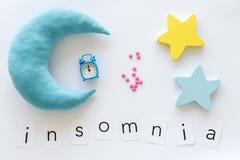 Palabra del insomnio, píldoras, luna, srars, alarma para la ayuda a bajar concepto dormido en la opinión superior del fondo blanc fotos de archivo