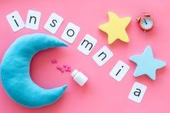 Palabra del insomnio, píldoras, luna, srars, alarma para la ayuda a bajar concepto dormido en la opinión superior del fondo del r fotografía de archivo