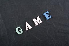 Palabra del JUEGO en el fondo negro compuesto de letras de madera del ABC del bloque colorido del alfabeto, espacio del tablero d Fotografía de archivo libre de regalías