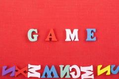 Palabra del JUEGO en el fondo rojo compuesto de letras de madera del ABC del bloque colorido del alfabeto, espacio de la copia pa Imagen de archivo