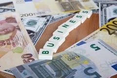 Palabra del negocio con las letras entre billetes de banco Fotografía de archivo libre de regalías