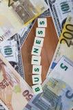Palabra del negocio con las letras entre billetes de banco Foto de archivo