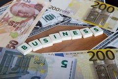 Palabra del negocio con las letras entre billetes de banco Foto de archivo libre de regalías