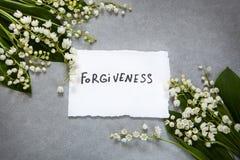 Palabra del perdón con las flores blancas fotografía de archivo libre de regalías