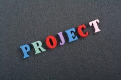 Palabra del PROYECTO en el fondo negro compuesto de letras de madera del ABC del bloque colorido del alfabeto, espacio del tabler Fotos de archivo libres de regalías