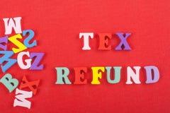 Palabra del REEMBOLSO de TEX en el fondo rojo compuesto de letras de madera del ABC del bloque colorido del alfabeto, espacio de  Fotografía de archivo