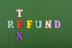 Palabra del REEMBOLSO de TEX en el fondo verde compuesto de letras de madera del ABC del bloque colorido del alfabeto, espacio de Fotos de archivo