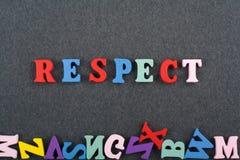 Palabra del RESPECTO en el fondo negro compuesto de letras de madera del ABC del bloque colorido del alfabeto, espacio del tabler Imágenes de archivo libres de regalías