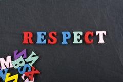 Palabra del RESPECTO en el fondo negro compuesto de letras de madera del ABC del bloque colorido del alfabeto, espacio del tabler Fotografía de archivo libre de regalías