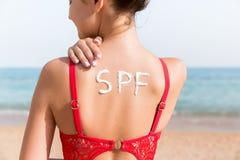 Palabra del SPF hecha de sunblock en la parte posterior de la mujer en la playa Concepto del factor de protecci?n de Sun fotografía de archivo libre de regalías