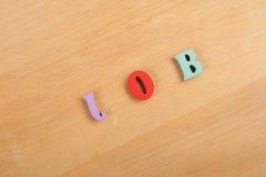 Palabra del TRABAJO en el fondo de madera compuesto de letras de madera del ABC del bloque colorido del alfabeto, espacio de la c Imagenes de archivo