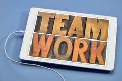 Palabra del trabajo en equipo en el tipo de madera en la tableta Foto de archivo libre de regalías
