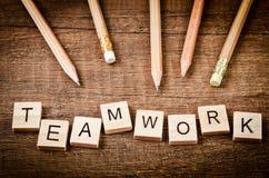 Palabra del TRABAJO EN EQUIPO escrita en el bloque de madera con los lápices de madera Fotografía de archivo libre de regalías