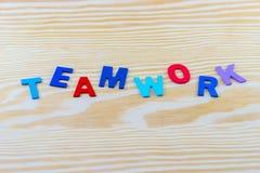 Palabra del TRABAJO EN EQUIPO escrita en el fondo de madera Foto de archivo