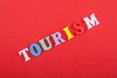 Palabra del TURISMO en el fondo rojo compuesto de letras de madera del ABC del bloque colorido del alfabeto, espacio de la copia  Fotos de archivo libres de regalías