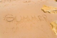 Palabra del verano en la arena en el playa como fondo Adultos jovenes Fotos de archivo libres de regalías
