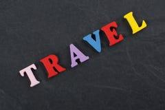 Palabra del VIAJE en el fondo negro compuesto de letras de madera del ABC del bloque colorido del alfabeto, espacio del tablero d Imagen de archivo