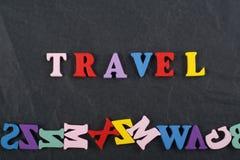 Palabra del VIAJE en el fondo negro compuesto de letras de madera del ABC del bloque colorido del alfabeto, espacio del tablero d Imagen de archivo libre de regalías