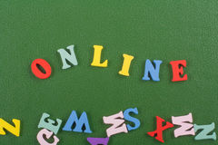 Palabra EN LÍNEA en el fondo verde compuesto de letras de madera del ABC del bloque colorido del alfabeto, espacio de la copia pa Foto de archivo