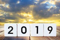 palabra 2019 en la caja de madera en un fondo de madera de la puesta del sol del tablón y del cielo imagenes de archivo