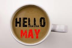 Palabra, escribiendo el hola mayo Texto de la primavera en café en taza Concepto del negocio para la prevención criminal de la se Foto de archivo