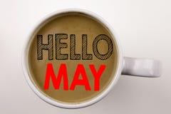 Palabra, escribiendo el hola mayo Texto de la primavera en café en taza Concepto del negocio para la prevención criminal de la se Fotografía de archivo