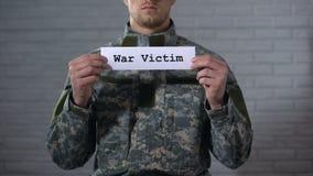 Palabra escrita en las manos masculinas del soldado de la muestra adentro, trastorno mental, trauma de la víctima de la guerra almacen de metraje de vídeo