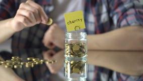 Palabra escrita sobre el tarro de cristal con el dinero, donaciones, fundación privada de la caridad almacen de metraje de vídeo