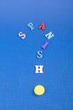 Palabra ESPAÑOLA en el fondo azul compuesto de letras de madera del ABC del bloque colorido del alfabeto, espacio de la copia par Foto de archivo