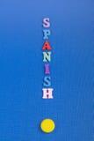 Palabra ESPAÑOLA en el fondo azul compuesto de letras de madera del ABC del bloque colorido del alfabeto, espacio de la copia par Imagenes de archivo
