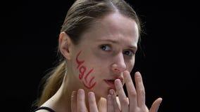 Palabra fea escrita en la cara femenina, señora que la cubre con las manos, estándares sociales almacen de metraje de vídeo