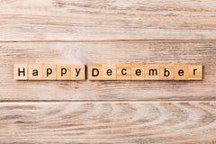 Palabra feliz de diciembre escrita en el bloque de madera Texto feliz en la tabla, concepto de diciembre imagen de archivo