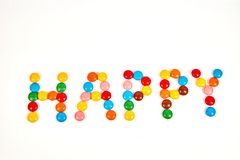 palabra feliz del caramelo colorido aislado en blanco imagenes de archivo