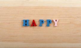 Palabra FELIZ en el fondo de madera compuesto de letras de madera del ABC del bloque colorido del alfabeto, espacio de la copia p Foto de archivo libre de regalías