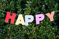 Palabra feliz por las letras en fondo de los árboles Imagen de archivo libre de regalías