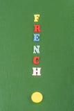 Palabra FRANCESA en el fondo verde compuesto de letras de madera del ABC del bloque colorido del alfabeto, espacio de la copia pa Fotografía de archivo libre de regalías