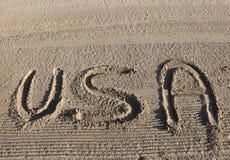 PALABRA grande los E.E.U.U. los Estados Unidos de América en la arena de la playa imagen de archivo