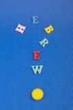 Palabra HEBREA en el fondo azul compuesto de letras de madera del ABC del bloque colorido del alfabeto, espacio de la copia para  Fotos de archivo libres de regalías