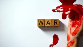 Palabra hecha de cubos de madera, mano que sangra en la tabla, conflicto pol?tico de la guerra fotografía de archivo